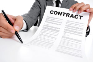 man wearing a suit sitting in a table showing a contract and where the signer must sign